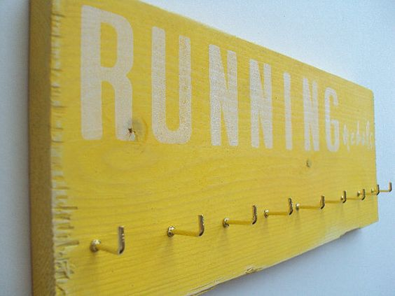 Fotos de uma parede com imagens bonitas, foto de uma planta num quarto branco, uma madeira amarela para pendurar objetos
